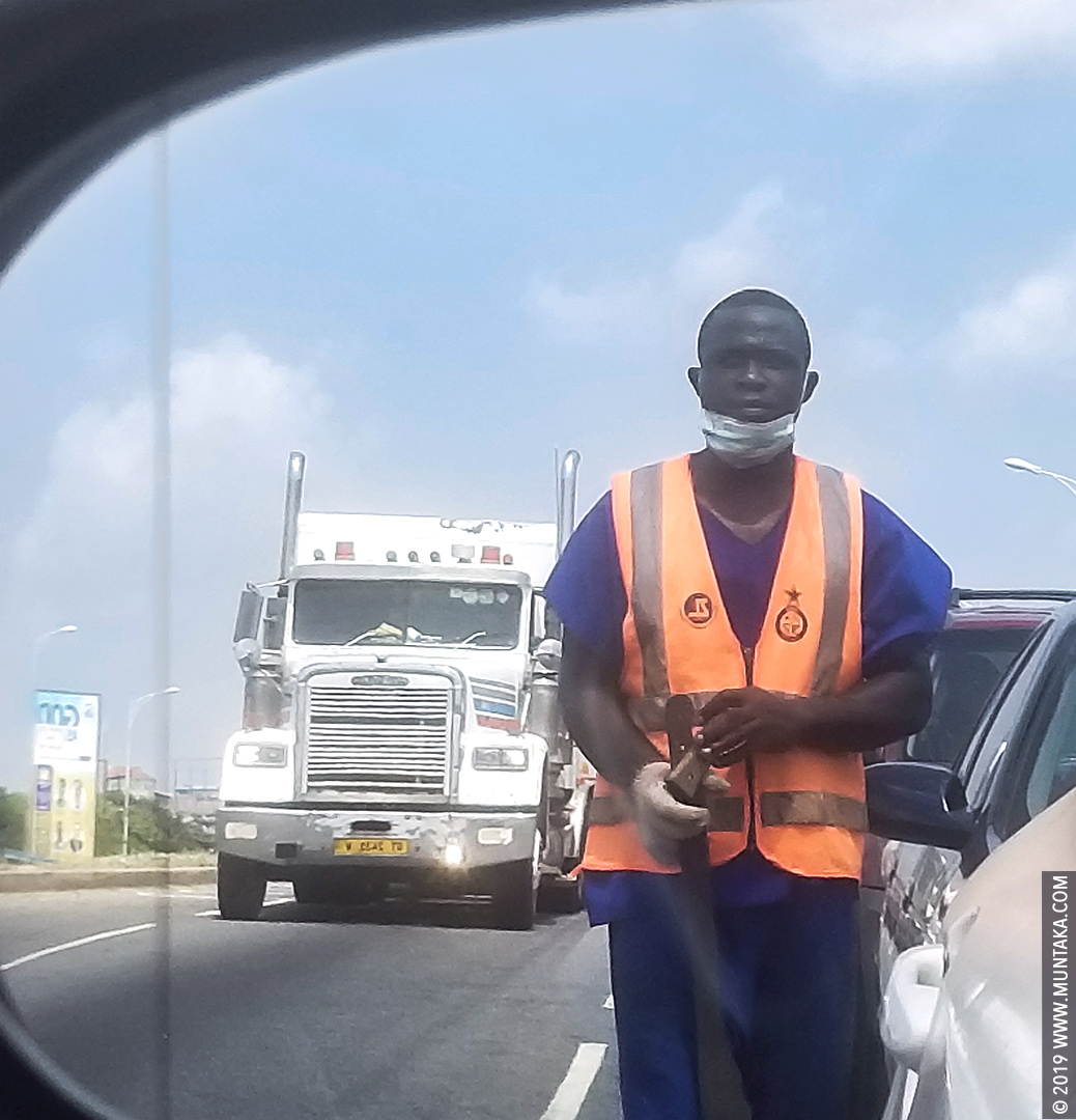 Ghana Prisoner Holding A Cutlass and Panhandling for Money on the Street of Accra, Ghana.