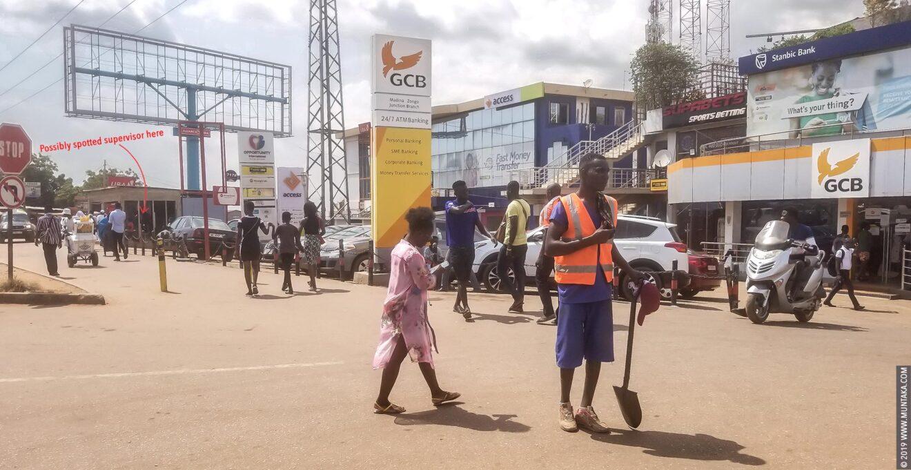 Ghana Prisoner in Orange Hazard Vest on top of a Blue Uniform Holding A Shovel and Panhandling for Money on the Street of Accra, Ghana. © 2019 Muntaka Chasant
