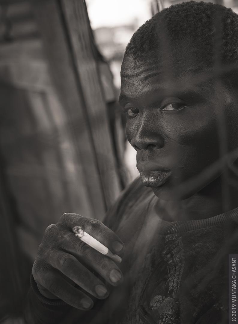 A man smoking a cigarette portrait.