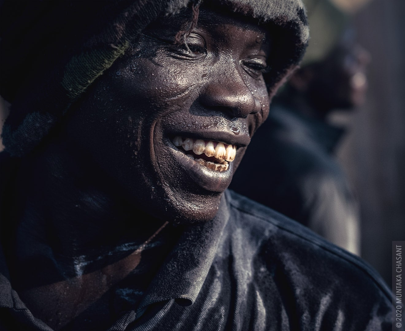 Man Smiling Photo: Smiling urban man portrait. Millions of young people in Africa with no education are forced to urban areas in search of greener pastures due to rural poverty. A lot of them end up in the informal sector, where they engage in all sorts of works. © 2020 Muntaka Chasant