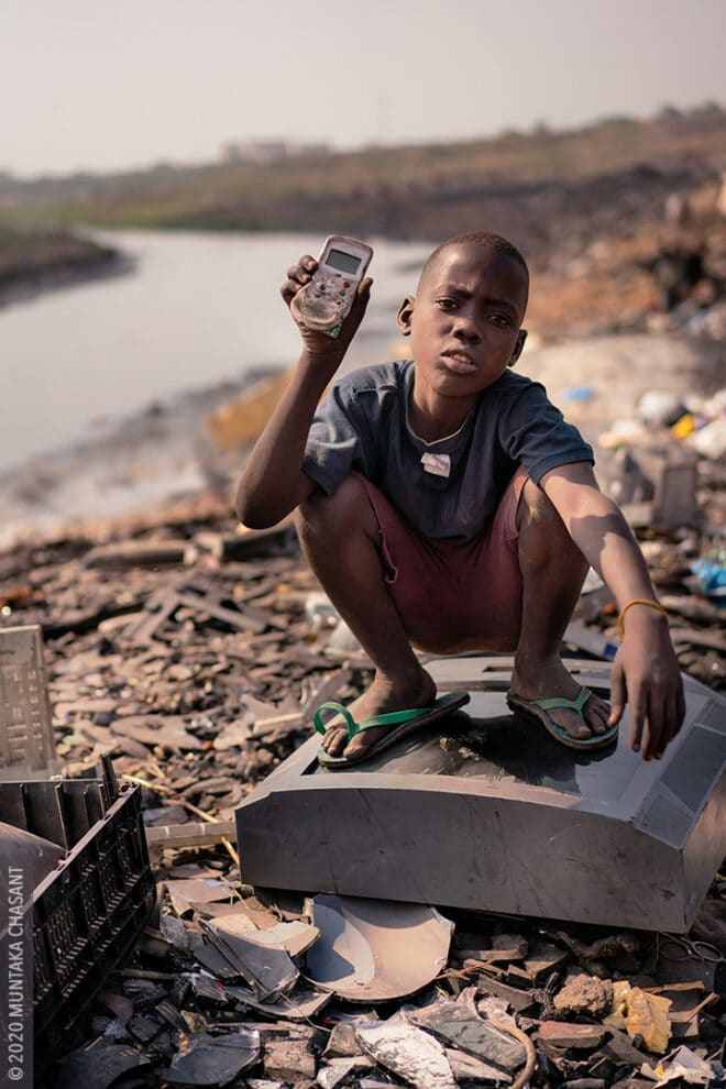 Agbogbloshie children: 12-year-old Twum is engaged in hazardous child labour at Agbogbloshie, Ghana. He uses his bare hands and stones to break apart e-waste for the precious metals inside. © 2020 Muntaka Chasant