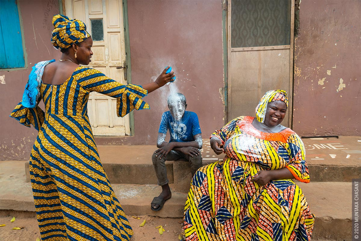 A family member is showering Malki with talcum powder. This signifies victory in most Ghanaian settings. Malik had lived and worked in a hazardous environment at Agbogbloshie August 2016 until February 19, 2020, when he reunited with his family. February 19, 2020. © 2020 Muntaka Chasant