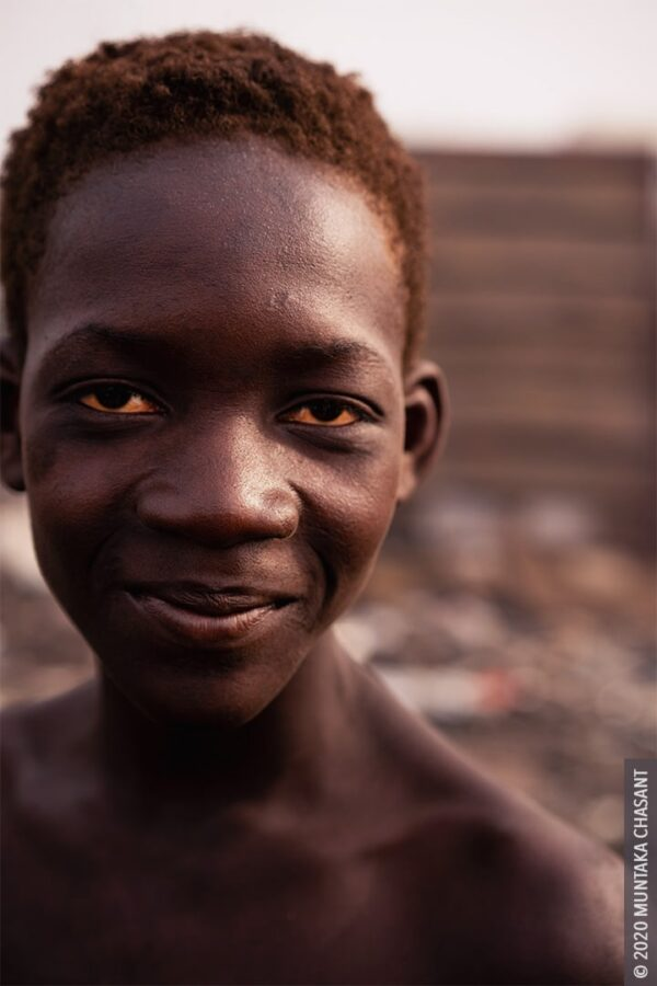 Smiling urban poor boy: 15 years old Kwabena — nicknamed Sugar Daddy — is a child labourer at Agbogbloshie, Ghana. © 2020 Muntaka Chasant
