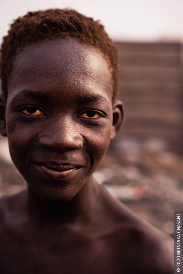 Smiling urban poor boy: 15 years old Kwabena (nicknamed Sugar Daddy) is a child labourer at Agbogbloshie, Ghana. © 2020 Muntaka Chasant