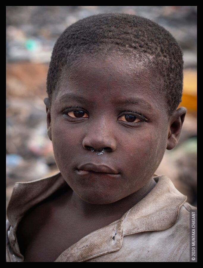 Poor Child: 'Akufo-Addo' is an 8 years old boy engaged in hazardous child labour on the fringes of Agbogbloshie, Ghana. According to the International Labour Organization, more than 75 million children who are victims of child labour worldwide are aged 5-11 years. Up to one-fourth of all hazardous child labour worldwide (19 million) is done by children less than 12 years old. Ghana has a high youth population, with people aged 24 years and below making up more than 55% of the population. According to UNICEF, around 28% of children in Ghana live in poverty. © 2020 Muntaka Chasant