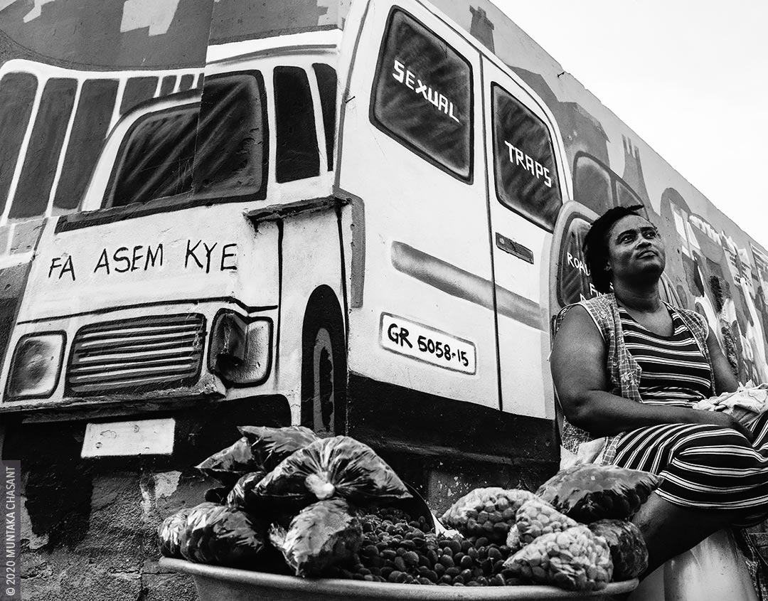 Urban poverty amid coronavirus outbreak: A street hawker sits in front of murals and sells African velvet tamarind in Accra Central, Accra, Ghana. This poor urban woman feels marginalized and complains of hunger and poverty amid the COVID-19 outbreak. 90% (8.3 million) of the currently employed population 15 years and older in Ghana are in the informal sector, with nearly 4.6 million being women. Many of them end up on the street doing petty works due to a lack of education. Nearly 42% of Ghana's population 3 years and older did not attend school at all because their family did not think school was necessary. Only 2.2% of Ghana's female population have a bachelor's degree. © 2020 Muntaka Chasant