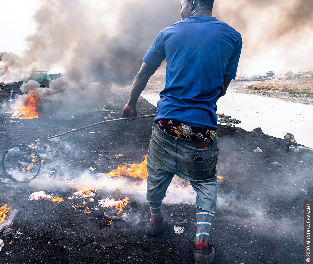 Agbogbloshie: A 'burner boy' is burning car steering wheels to reclaim the aluminium inside. © 2020 Muntaka Chasant