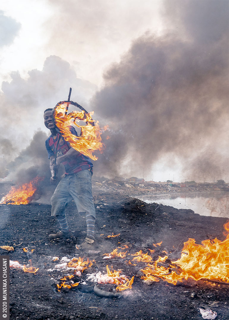 "Agbogbloshie: Man is burning car steering wheels to reclaim the aluminium materials inside. They call it ""Korea Aluminium"" at Agbogbloshie, and sold for around GH₵1.5 ($0.25) per pound in May 2020. © 2020 Muntaka Chasant"