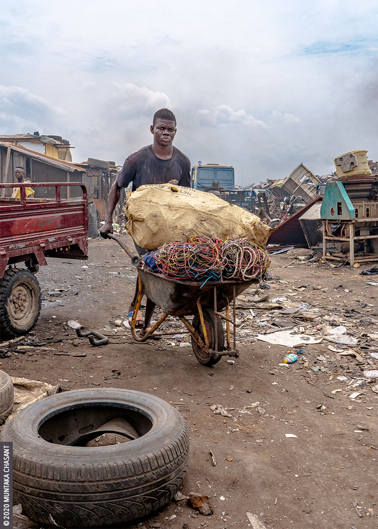Agbogbloshie: man is transporting cables in a wheelbarrow to be openly incinerated for the copper materials inside. © 2020 Muntaka Chasant