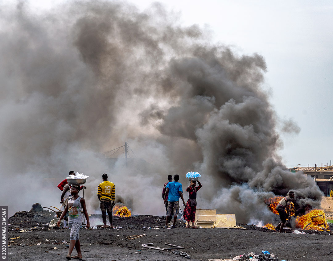 Agbogbloshie in May 2020: Young urban poor men are burning insulated wires in the open to recover the copper materials inside near the center of Accra, Ghana's capital city. © 2020 Muntaka Chasant