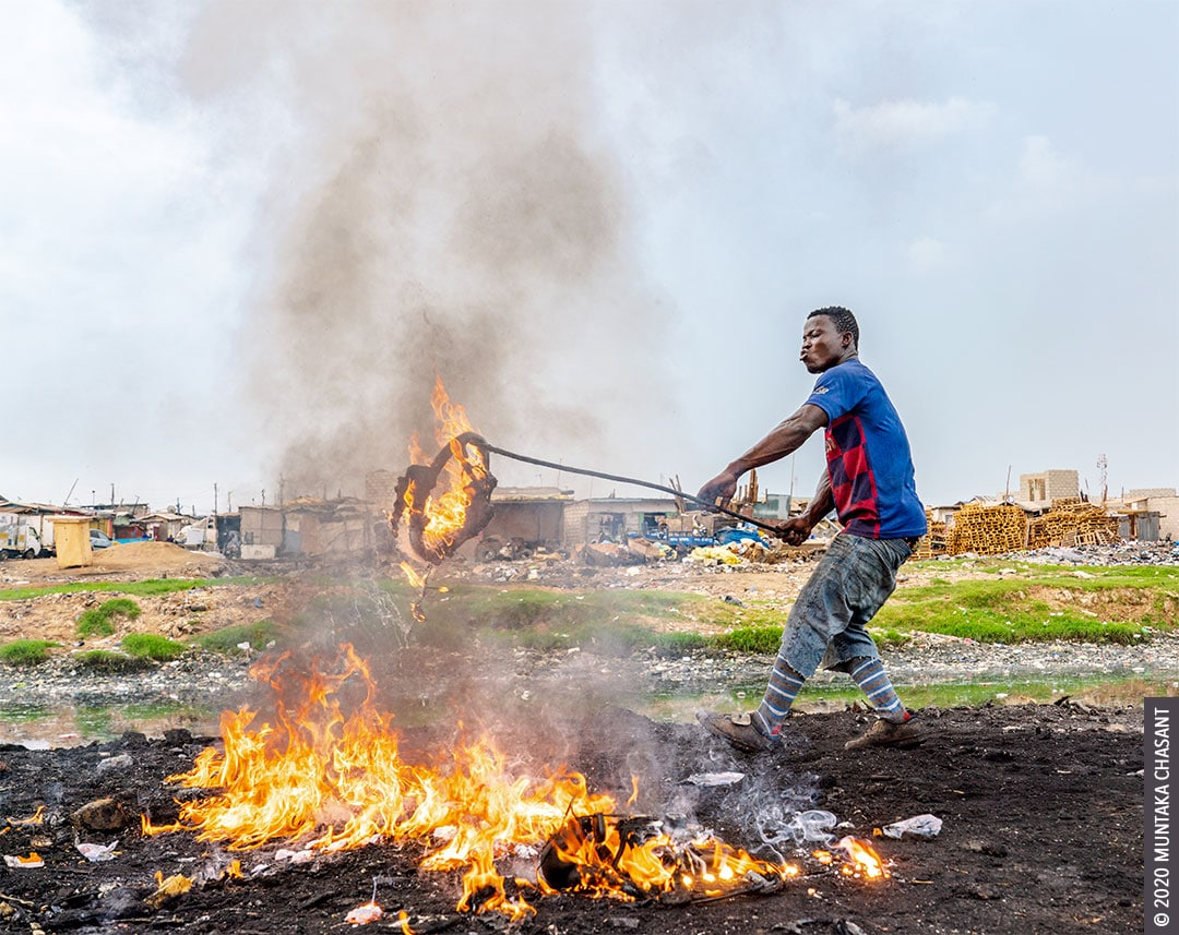 Agbogbloshie: Young man is openly burning auto steering wheels to recover the 'Korea' aluminium inside. © 2020 Muntaka Chasant