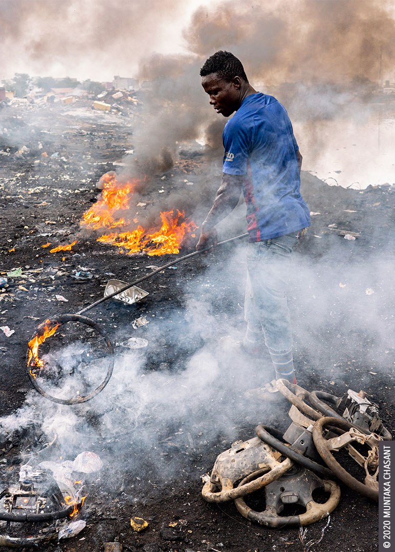 Man is burning car steering wheels to recover the 'Korea' aluminium inside at Agbogbloshie, Ghana. © 2020 Muntaka Chasant