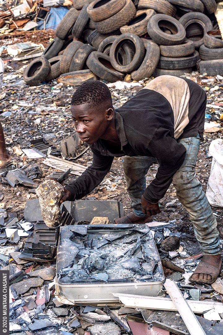 Informal CRT TV recycling: Man is using a rock to break apart an old CRT TV to reclaim the iron materials inside at Agbogbloshie, Ghana. © 2020 Muntaka Chasant