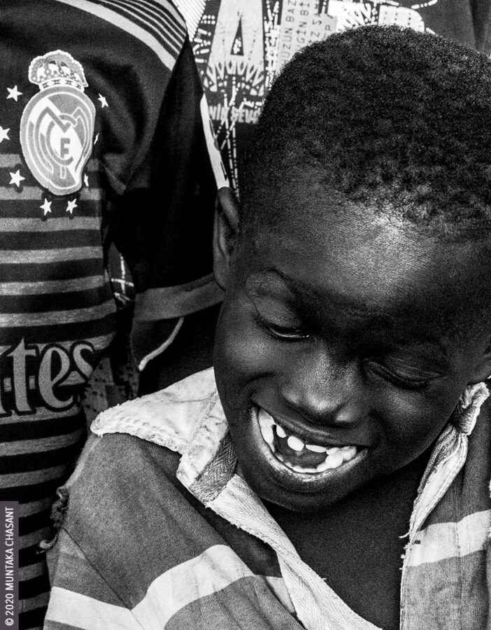 Child Poverty: Smiling Kwadwo Michael is a 7 years old urban poor who lives on the fringes of Agbogbloshie, Ghana. He uses his bare hands and stones to break apart e-waste for the precious metals inside, exposing himself to heavy metals such as lead, mercury, cadmium, and arsenic. Worldwide, 73 million children between 5 and 17 years are in hazardous child labour, according to the ILO. © 2020 Muntaka Chasant