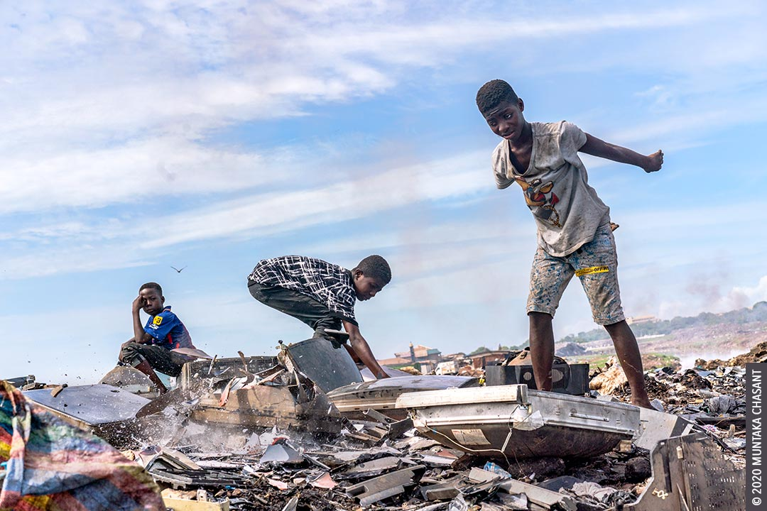 Child labour and electronic waste: A 15-year-old adolescent boy had just smashed an old CRT TV against a rock to reclaim the shadow mask inside at Agbogbloshie, Ghana. © 2020 Muntaka Chasant