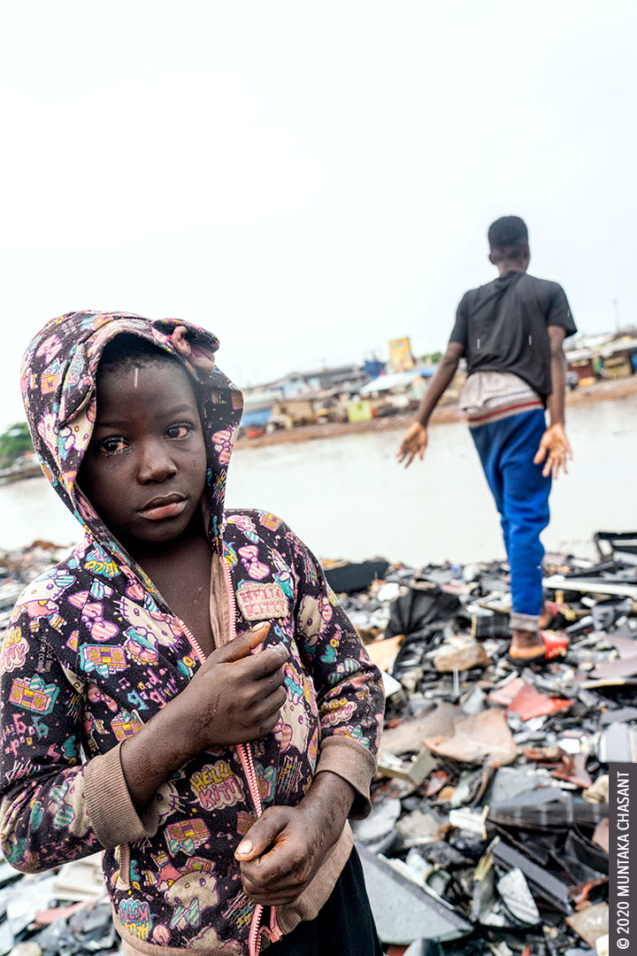 Child labour: An 8-year-old urban poor boy nicknamed after Ghana's current president is working in the rain. 'Akufo-Addo' is engaged in hazardous child labour in Accra, Ghana's capital city. Behind him: Debrah, 15 years old, had just smashed a CRT TV against a rock to recover the iron materials inside. Nearly 2 million children in Ghana are in child labour. More than 70 million children worldwide are in hazardous child labour. © 2020 Muntaka Chasant