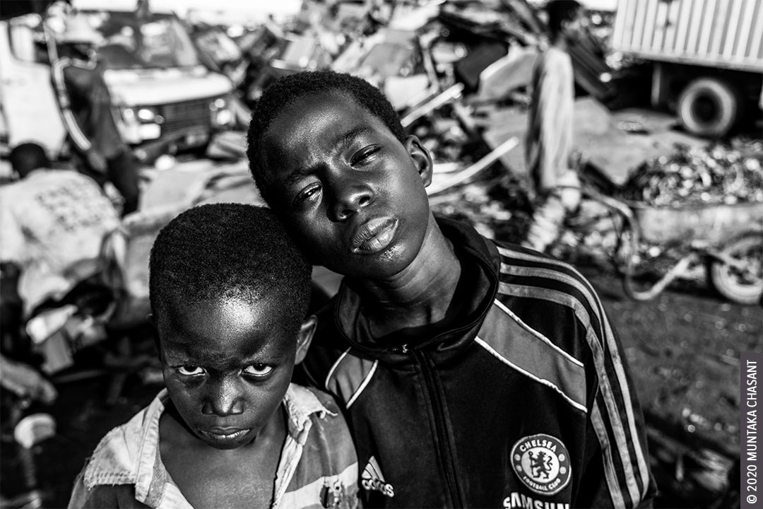 Children in Poverty: Kwadwo Michael, 7 years old, and Kwaku Frimpong, 12 years, are children in poverty who live on the margins of Agbogbloshie, Ghana. They do all sorts of e-waste related works, including using their bare hands and stones to break apart e-waste for the precious metals inside. Worldwide, 62% of all children in hazardous child labour are boys, the ILO statistics show. © 2020 Muntaka Chasant