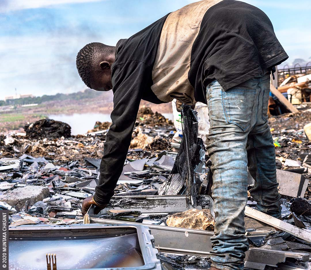 Electronic waste recycling: Joseph Akwah, 17 years old, is using his bare hands to dismantle an old CRT TV to reclaim the iron materials inside at Agbogbloshie, Ghana. © 2020 Muntaka Chasant