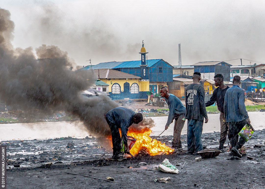 Fire and rain image: Young poor men burn cables in the rain to reclaim the copper materials inside at Agbogbloshie, Ghana. © 2019 Muntaka Chasant