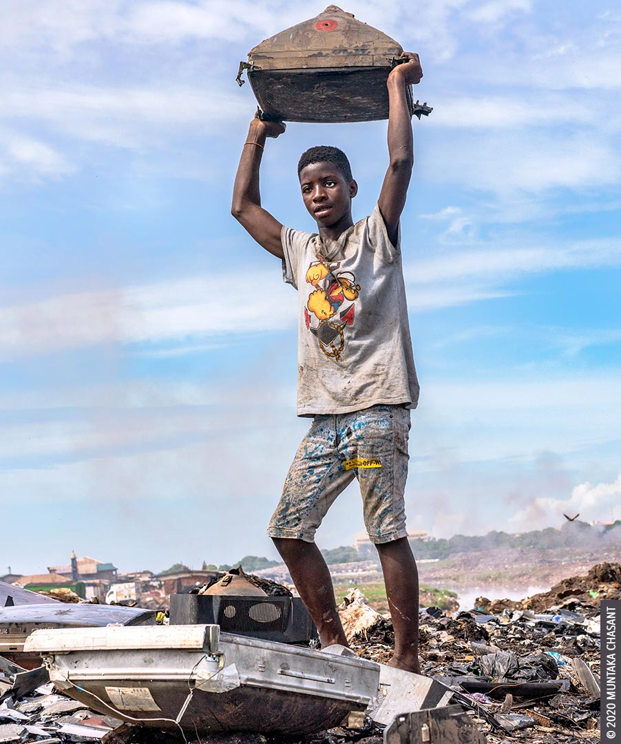 Hazardous child labour picture: A 15-year-old boy who wears an artificial eye on the left side is getting ready to smash an old CRT TV against a rock to reclaim the shadow mask and other iron materials inside. © 2020 Muntaka Chasant