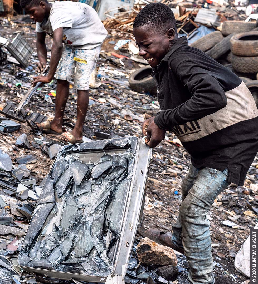 Hazardous child labour: 17-year-old adolescent boy is breaking apart an old CRT TV to reclaim the iron-nickel alloy materials inside at Agbogbloshie, Ghana. The minimum age for hazardous work in Ghana is 18, according to Section 91 of Ghana's Children's Act (560). © 2020 Muntaka Chasant