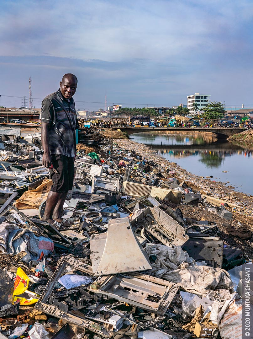 Urban Poverty in Africa: An urban poor Nigerian man is singing and cannibalizing from discarded e-waste at Agbogbloshie, Ghana. 41% of people in Africa live in extreme poverty, World Bank data shows. © 2020 Muntaka Chasant