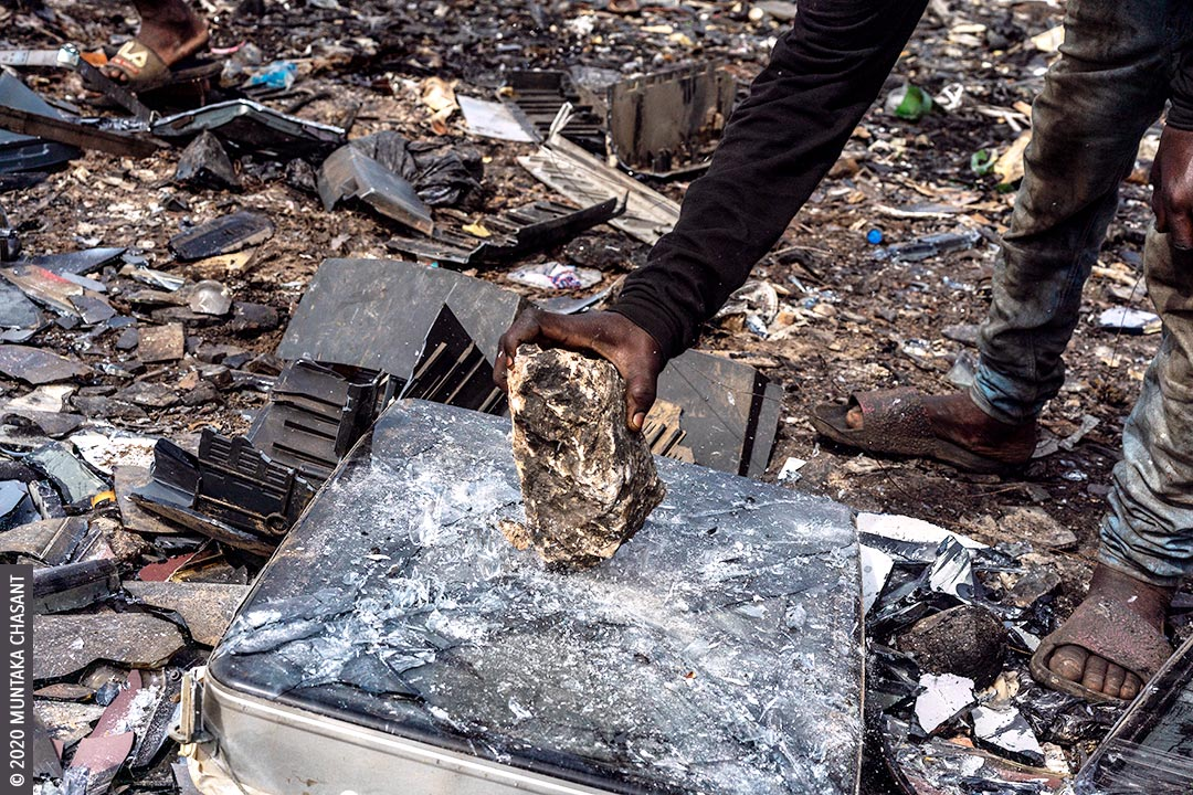 Primitive e-waste recycling: Man is using a rock to break apart an old CRT TV to reclaim the iron materials inside at Agbogbloshie, Ghana. © 2020 Muntaka Chasant