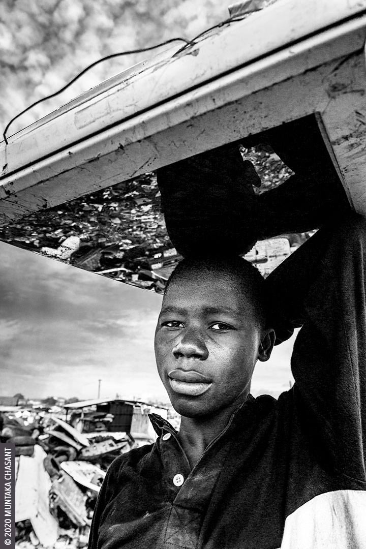 "Urban mining: 17-year-old Akwah is carrying an old CRT TV on his head at Agbogbloshie, Ghana. The old television set was ""urban mined"" for iron materials. © 2020 Muntaka Chasant"