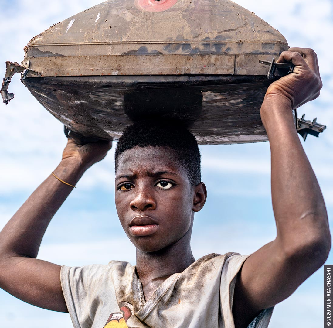Urban poverty: 15-year-old Kwaku Debrah is an urban poor boy engaged in hazardous child labour on the fringes of Agbogbloshie, Ghana. He's blind in the left eye and wears a prosthetic. According to a recent report, more than 62% of urban children in Ghana aged 0 -17 years are multidimensionally poor (deprivations such as lack of proper nutrition, basic sanitation, and housing). © 2020 Muntaka Chasant