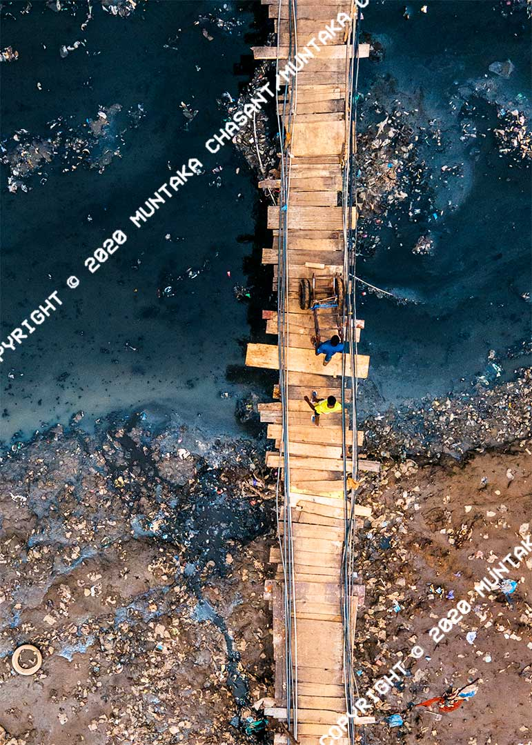 Aerial view of a makeshift wooden bridge at the Sodom and Gomorrah (Agbogbloshie) slum in Accra, Ghana. Copyright © 2020 Muntaka Chasant