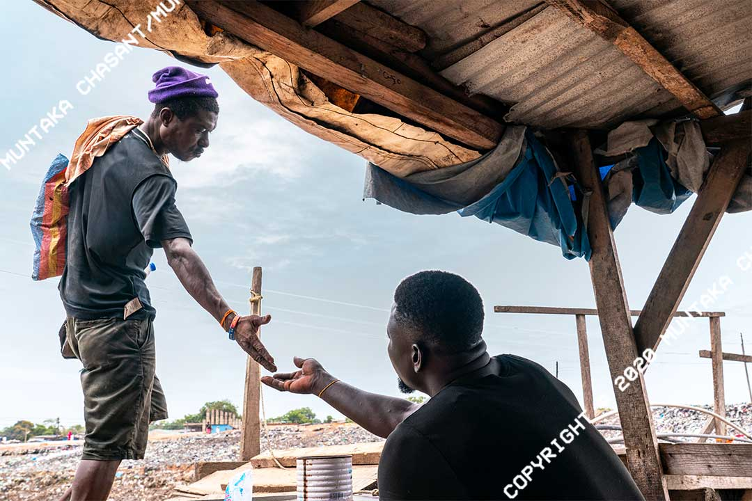 Man pays a toll to cross a makeshift wooden bridge. Sodom and Gomorrah (Agbogbloshie) slum, Accra, Ghana. Copyright © 2020 Muntaka Chasant