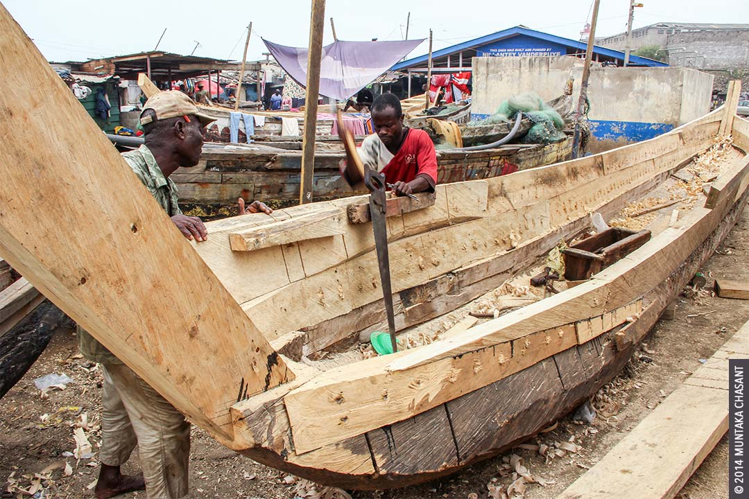 Canoe building: Men build a fishing canoe at the Jamestown fish landing site in Accra, Ghana. Copyright © 2014 Muntaka Chasant