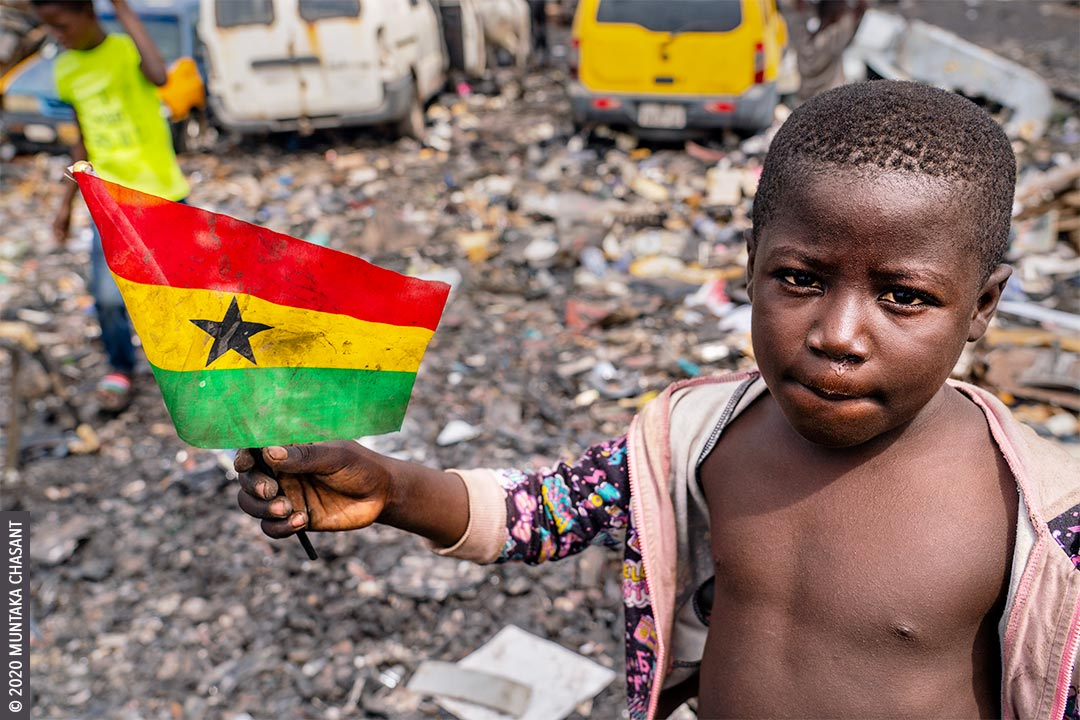 An 8-year-old boy nicknamed after Ghana's current president and engaged in hazardous child labour in Accra is holding a Ghana flag. © 2020 Muntaka Chasant