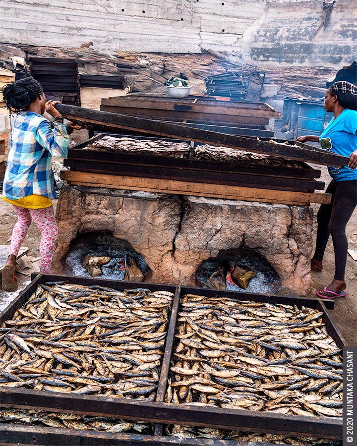 Fish processing in Ghana: Two young Ghanaian women use chorkor oven to smoke fish in Accra, Ghana. Chorkor oven exposes fish smokers to air toxicants such as polycyclic aromatic hydrocarbons, respirable particulate matter, and carbon monoxide. Copyright © 2020 Muntaka Chasant