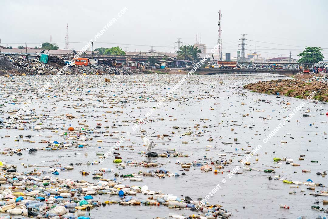 Plastic pollution in Accra, Ghana: Plastic waste floats on the surface of the Korle Lagoon in Accra during a rainfall. The majority of the plastics end up in the ocean. Around 80% of the plastics in the ocean come from land-based sources, according to a 2016 study. Copyright © 2020 Muntaka Chasant