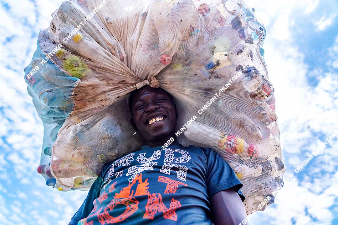 Man smiling: An urban poor man smiles after collecting plastics from the polluted Korle Lagoon for recycling. Only around 5% of the 1 million tonnes of plastic waste generated in Ghana are recycled. Copyright © 2020 Muntaka Chasant