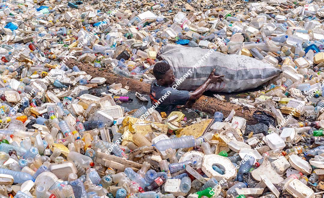 Plastic pollution in Ghana: An urban poor man in the heavily polluted Korle Lagoon collects plastics to sell. Around 1 million tonnes of plastic waste is generated in Ghana every year. Copyright © 2020 Muntaka Chasant