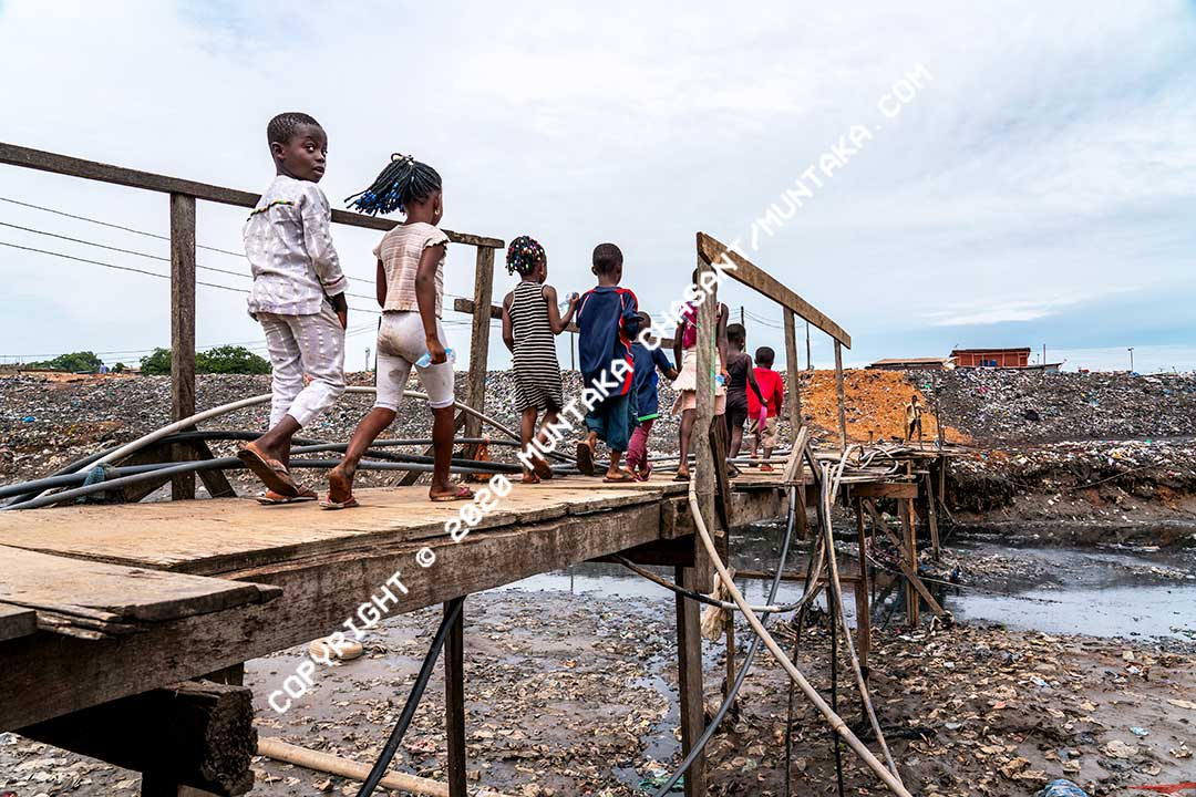 Slum children: Sodom and Gomorrah (Agbogbloshie) slum children walk on a precarious makeshift wooden bridge across the Agbogbloshie drain. More than 60% of children between 0-17 years in Ghana are multidimensionally poor — including lack of access to basic sanitation, healthcare, and security. Copyright © 2020 Muntaka Chasant