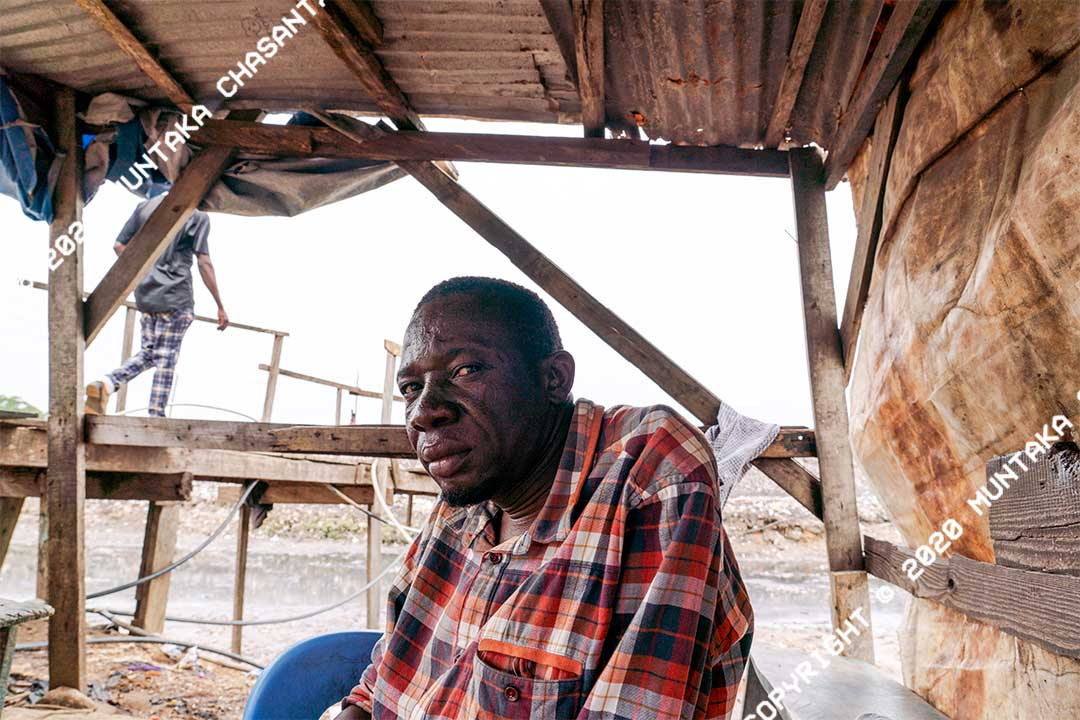 Portrait of an Agbogbloshie slum entrepreneur who built a makeshift wooden bridge to connect his community to nearby areas. Accra, Ghana. Copyright © 2020 Muntaka Chasant