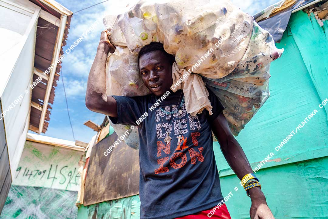 An urban poor man in Accra carries plastic bottles he had collected from the surface of the heavily polluted Korle Lagoon in Accra, Ghana. Copyright © 2020 Muntaka Chasant