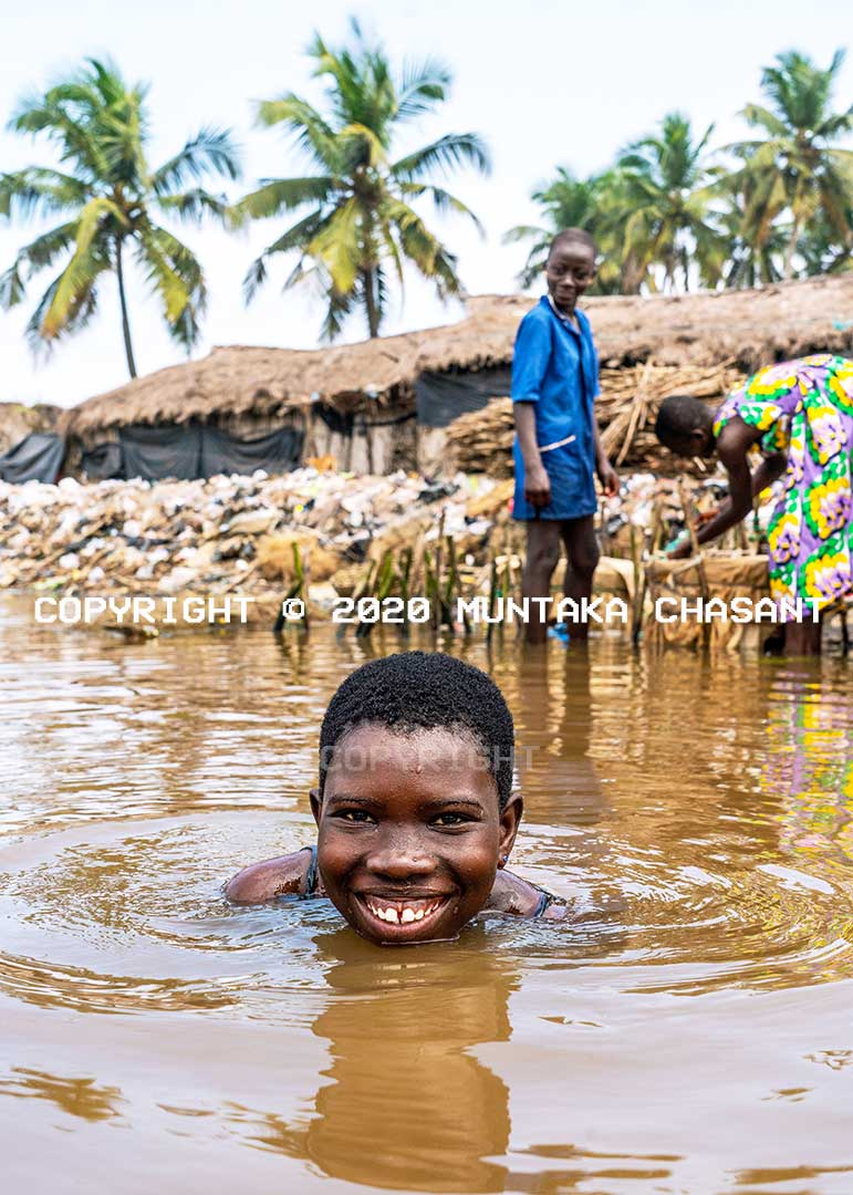 A pretty young African woman swim and smile in a lagoon in Ghana. Copyright © 2020 Muntaka Chasant