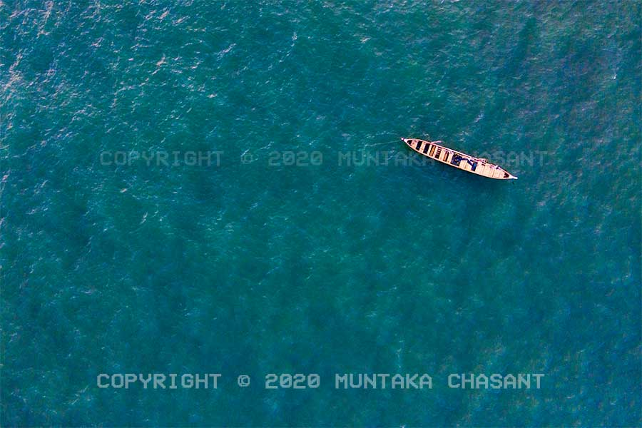 Gulf of Guinea: A fishing canoe in the Gulf of Guinea (northeasternmost part of the tropical Atlantic Ocean). About half a mile off the coast of Accra, Ghana's capital city. Mavic Air 2 Drone Photography. Copyright © 2020 Muntaka Chasant