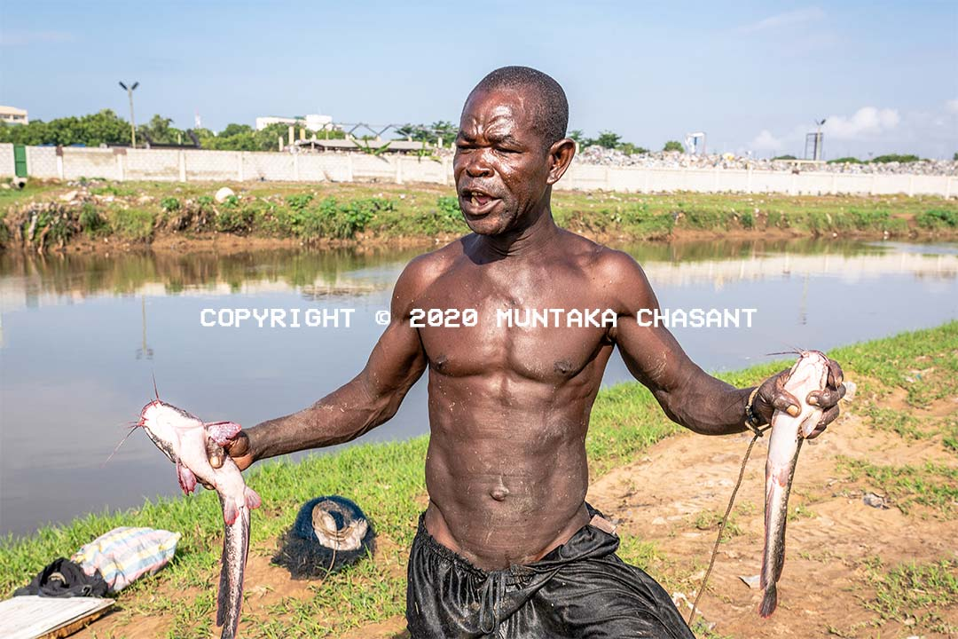 Plastic pollution: Urban poor fisherman is angry that plastic waste from Accra is destroying their livelihoods. Nii Aryee, 54 years old, is fishing for catfish in the heavily Korle Lagoon near the Gulf of Guinea. Accra, Ghana. Copyright © 2020 Muntaka Chasant