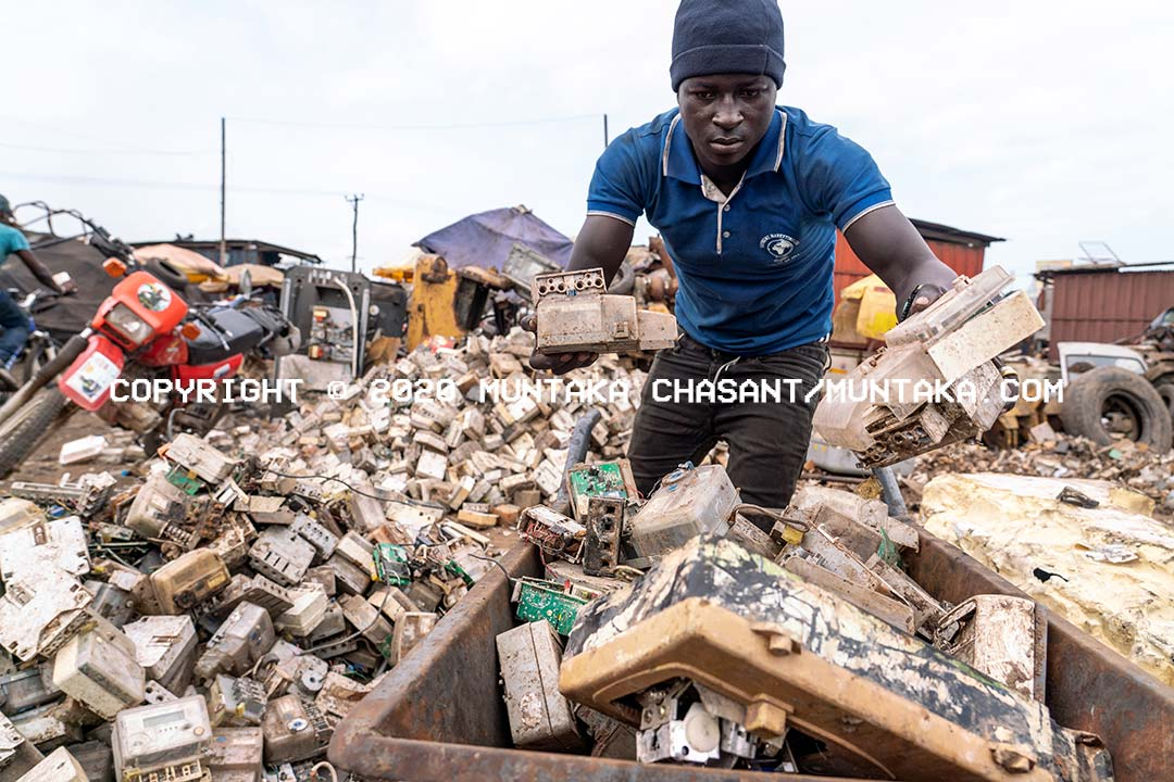 Agbogbloshie crap worker loads energy meters onto a wheelbarrow. Agbogbloshie, Ghana. Copyright © 2020 Muntaka Chasant