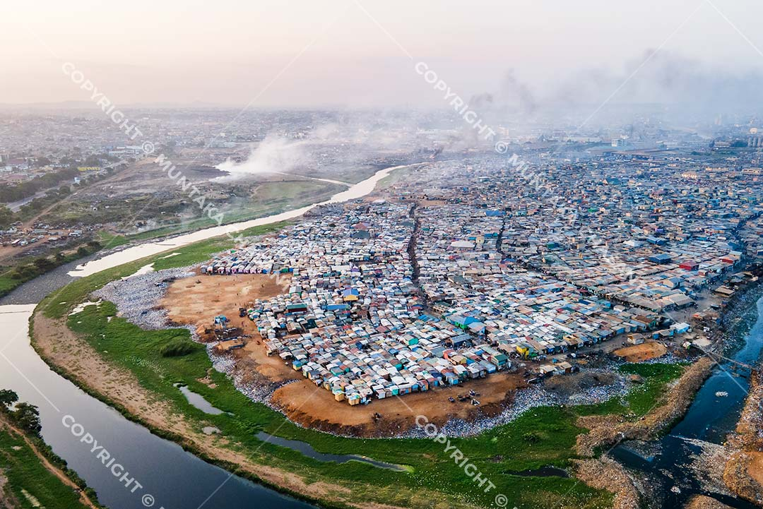 12 August 2020 — Aerial view of Agbogbloshie and the u-shaped Korle Lagoon with the Sodom and Gomorrah settlement in the middle. More than 70,000 urban poor live inside the Sodom and Gomorrah slum (also known as Old Fadama). Copyright @ 2020 Muntaka Chasant