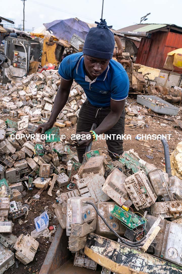 Agbogbloshie e-waste miner loads ECG electricity meters onto a wheelbarrow. Copyright © 2020 Muntaka Chasant