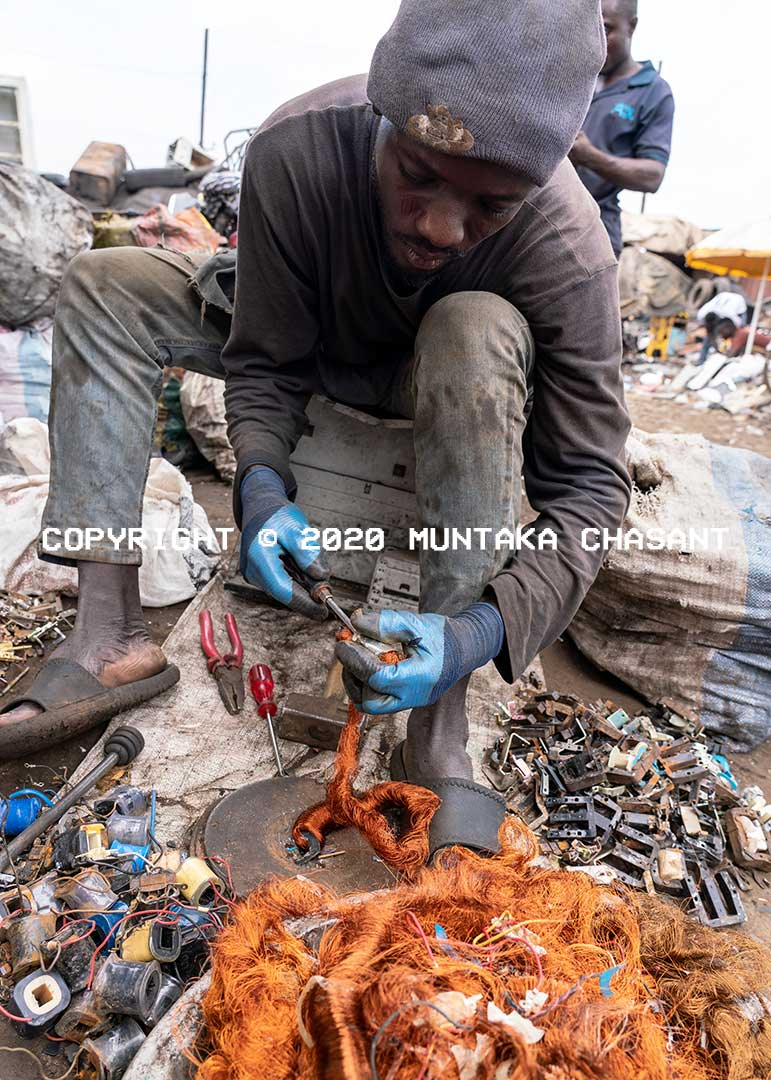 Urban poor man covering copper from electronic transformers at Agbogbloshie, Ghana. Copyright © 2020 Muntaka Chasant