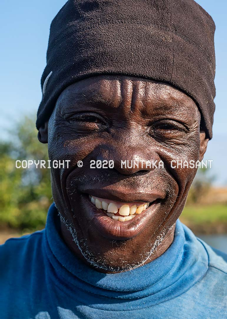 African man smile: Older African man who uses bottles to catch small blackchin tilapia in Ghana smiles for the camera. Copyright © 2020 Muntaka Chasant