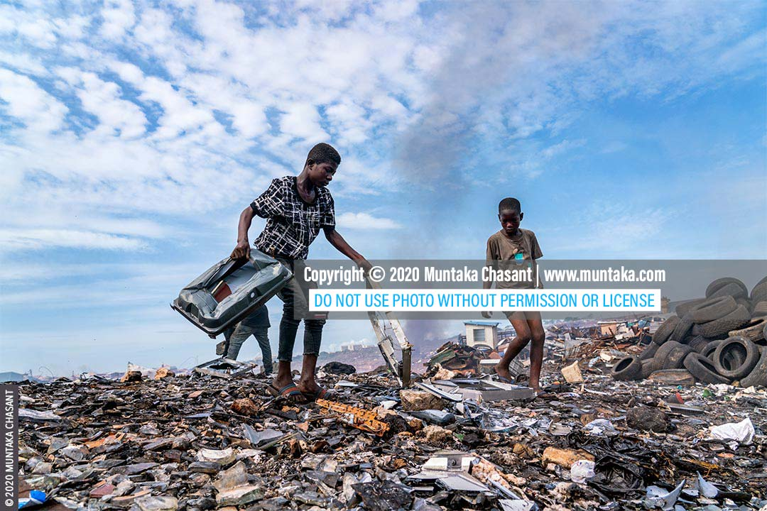 Children working in a toxic environment: Osei, 15 years, and Mustafa, 13 years, are using stones to break apart old television sets to reclaim the iron materials inside at Agbogbloshie, Ghana. © 2020 Muntaka Chasant
