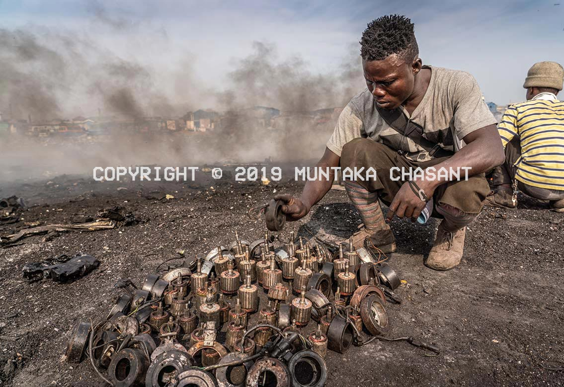Agbogbloshie recycling: Man about to burn armature and other materials to recover copper. Copyright © 2019 Muntaka Chasant